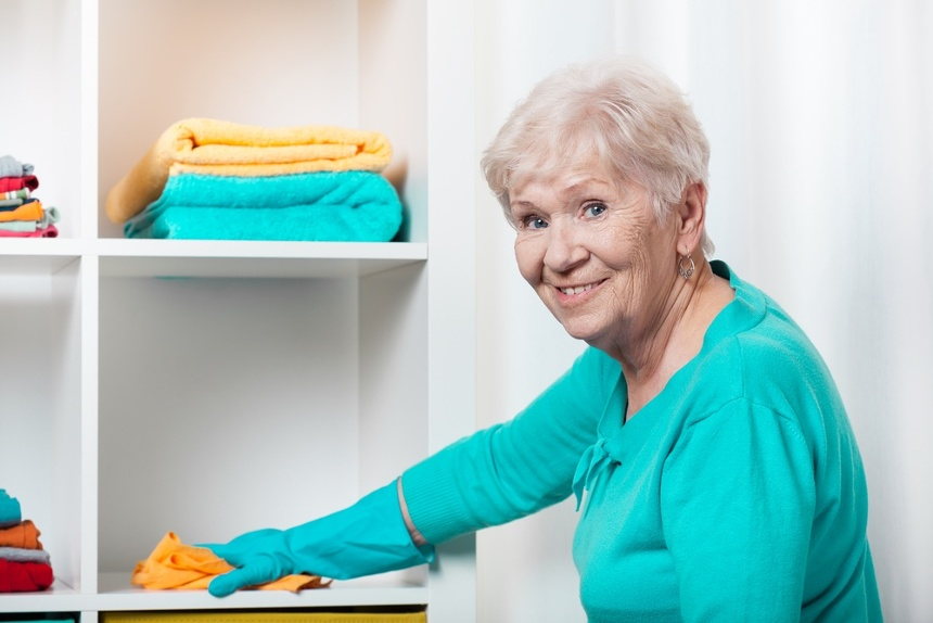 Smiling senior woman cleaning house before Christmas